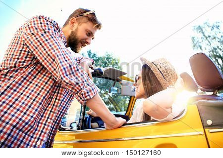 Couple in convertible. Beautiful young couple enjoying road trip in their convertible and looking at each other with smile