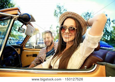 Happy to travel together. Joyful young couple smiling while riding in their convertible