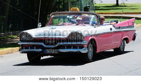 Varadero, Cuba - September 11, 2016:  pink American Cabriolet Classic Car Dirves in Varadero City, Cuba