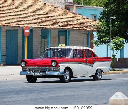 Varadero, Cuba - September 11, 2016:  Red and white American Classic Car Dirves in Varadero City, Cuba