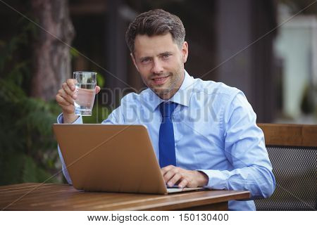 Handsome businessman having drink while using laptop at outdoor caf\x96\xA7