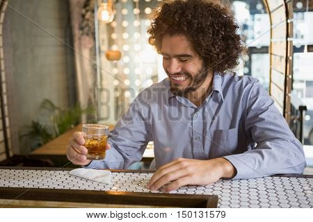 Man having glass of whisky in bar counter at bar