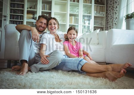 Happy family sitting on the rug in living room at home