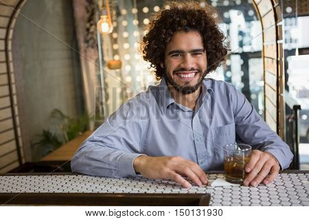 Portrait of man sitting on bar counter with glass of whisky in bar