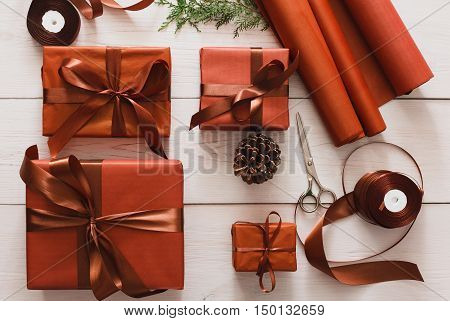 Gift wrapping. Packaging stylish christmas present boxes in maroon paper decorated with satin ribbon bows. Christmas and winter holidays concept, top view, flat lay