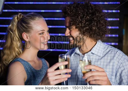 Smiling couple toasting a glass of champagne in bar