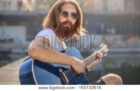 Fashionable man playing the guitar