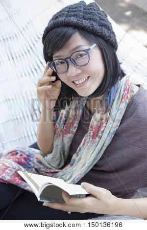 asian woman and pocket book in hand relaxing on home cradle