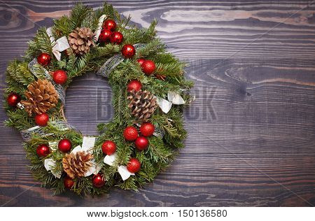 Christmas wreath and ribbon bow on a wooden background.