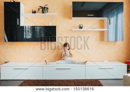 child (girl) sitting on twine (split) on furniture. training