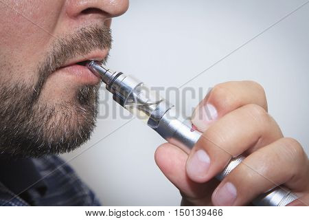 Profile view of man smoking electronic sigarette close up