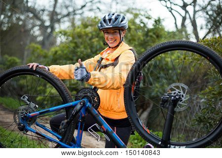 Female biker showing thumbs up while repairing mountain bike in countryside
