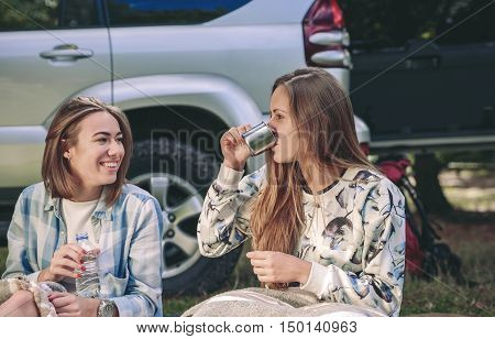 Portrait of young woman drinking cup of coffee with her friend sitting under blanket in campsite