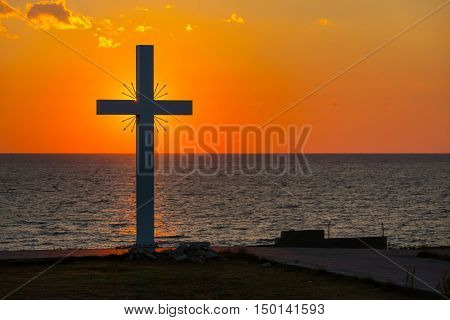 Silhouette of cross at sunrise or sunset with light rays and sea panorama, Greece