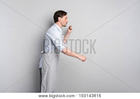 Taste it. Joyful handsome man pretending like tasting something with a spoon while standing on a grey background