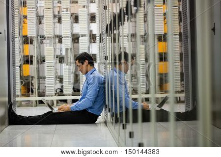 Technician working on laptop in hallway of server room