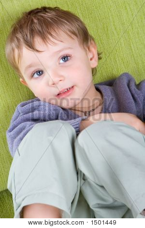 Little Boy Resting On A Sofa.