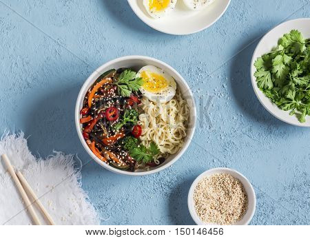 Noodles with vegetable stir fry and boiled egg. Vegetarian food in asian style. On a blue background top view