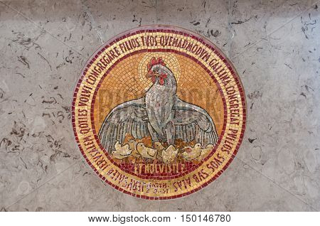 Detail of mosaic in church including a chicken with chicks and bible verse