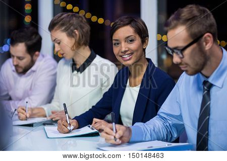 Businesspeople preparing document in office at night