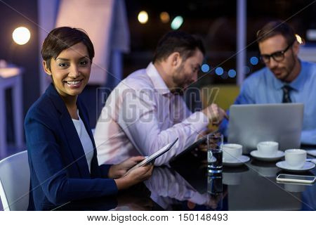Businesswoman using digital tablet with colleagues in background in office