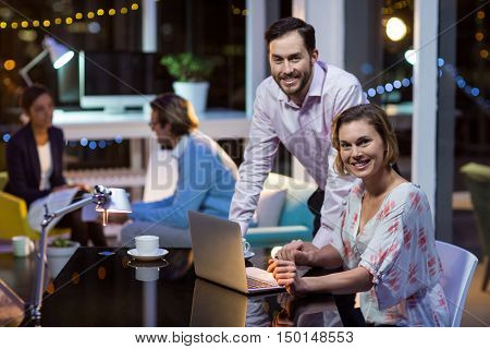 Portrait of businesspeople using laptop in office at night