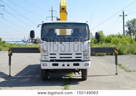 A White Isuzu flatbed truck with yellow crane arm is in the parking lot - Russia Moscow 30 August 2016