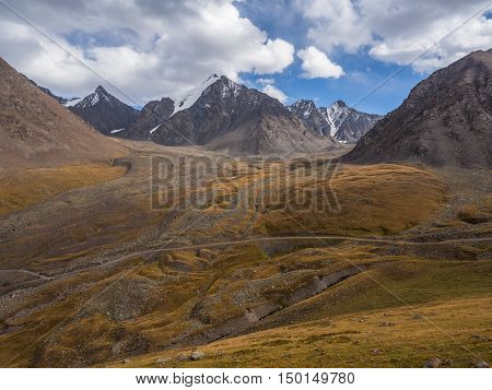 Alpine meadow in Kyrgyzstan mountains with river and serpentine road