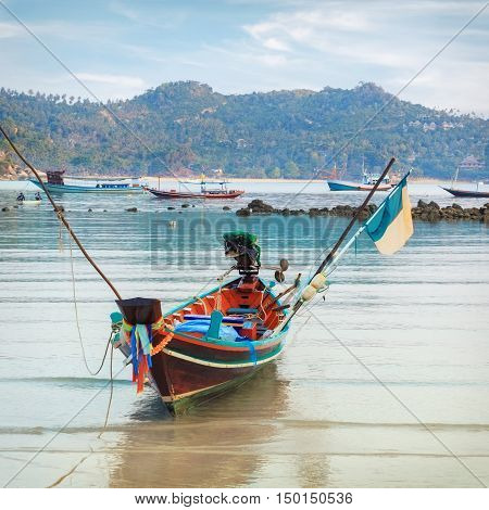 wooden colorful long tail boat on tropical beach of Thailand
