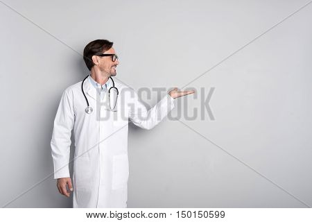 Medicine inspires. Handsome smiling young doctor standing on a grey backgrouns holding a stethoscope while gesturing.