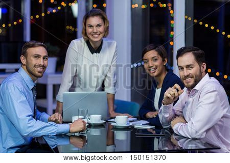 Portrait of smiling businesspeople in office at night