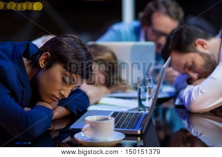 Tired businesspeople sleeping in office at night