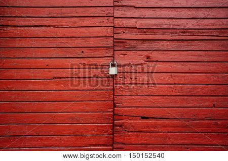 Old red wooden door closed with the padlock