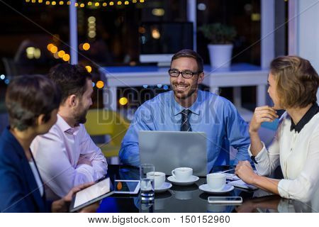 Businesspeople interacting with each other in office at night