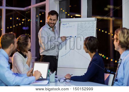 Businessman discussing graph on whiteboard with colleagues in office at night