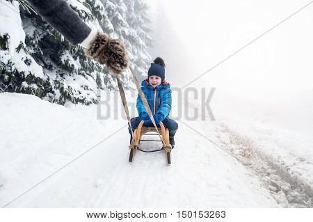Unrecognizable mother pulling her son on sledge, foggy white winter nature.