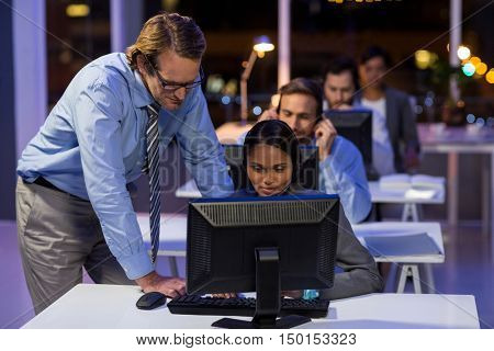 Businessman assisting his colleague in office at night