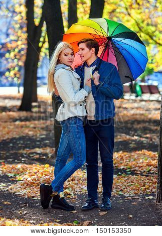 Happy young couple embracing under umbrella in autumn day. Fall weather is crisp.