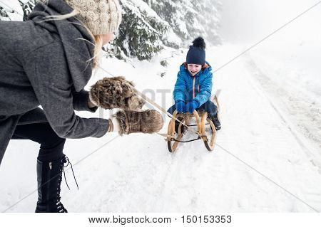 Unrecognizable young mother pulling her son on sledge, foggy white winter nature.