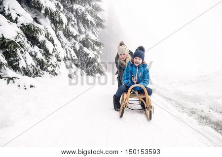 Beautiful young mother pushing her son on sledge, foggy white winter nature.