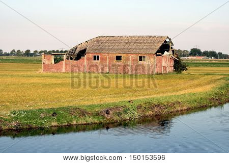 An old barn partially decayed. On a field near water.