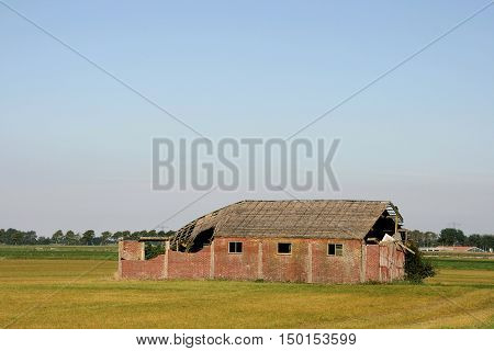 An old barn partially decayed. On a field.