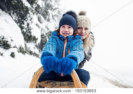 Beautiful young mother with her son on sledge, foggy white winter nature. Close up.