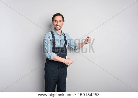 Involved in work. pleasant man smiling and standing against grey background while working