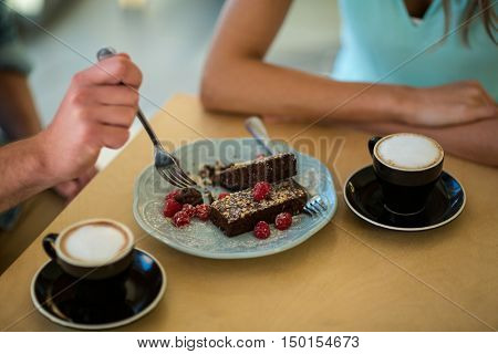 Mid-section of couple eating pastry in caf\x92\xA9