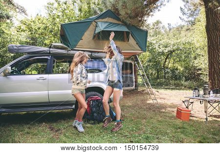 Young women friends having fun in a campsite into the forest. Leisure time and enjoyment concept.