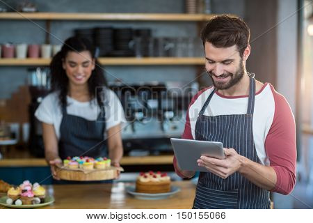 Smiling waiter using digital tablet at counter in caf\x92\xA9