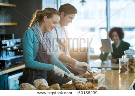 Smiling waiter and waitress working at counter in caf\x92\xA9