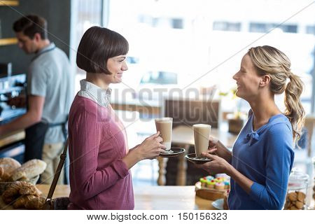 Female friends interacting while having a cup of coffee in caf\x92\xA9