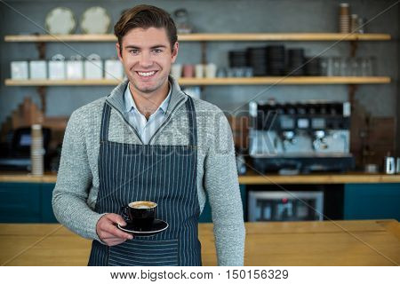 Portrait of waiter holding cup of coffee in caf\x92\xA9